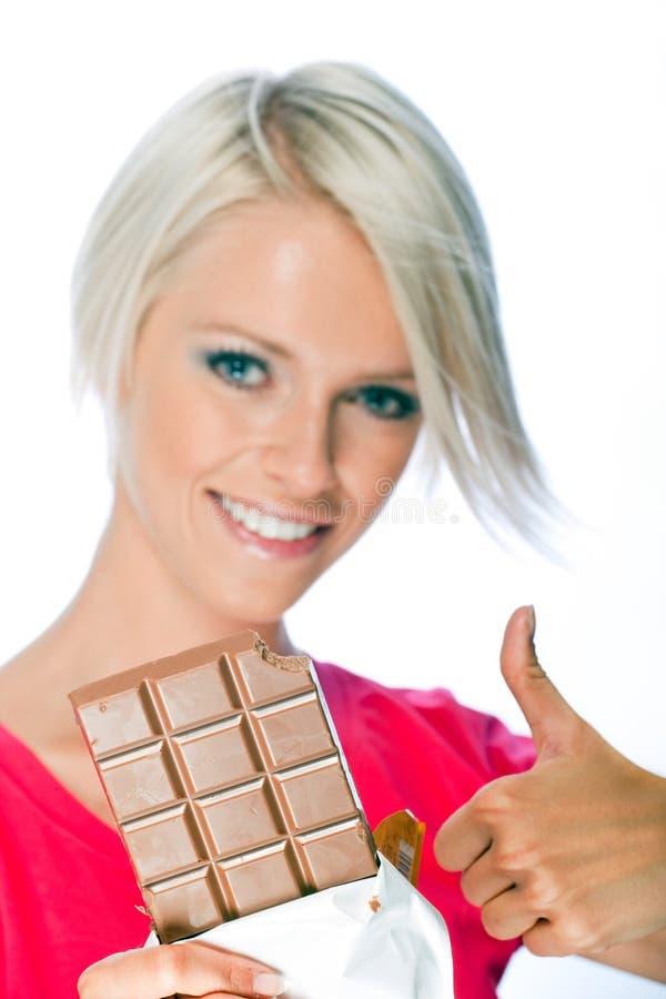 Gladlynt blond kvinna som rymmer en chokladstång arkivbild