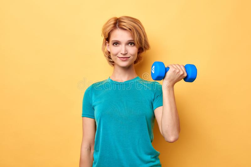 Gladlynt blond kvinna som rymmer vikter isolerade på gul bakgrund arkivbild