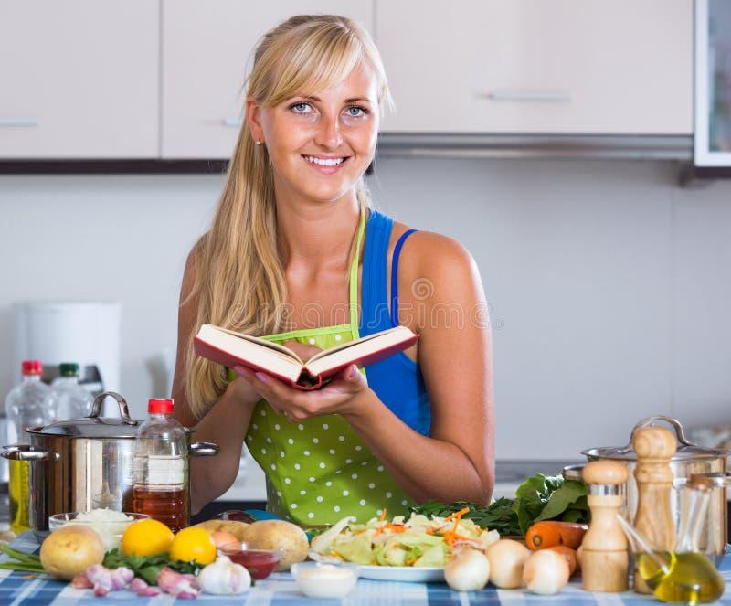 Gladlynt blondie som förbereder veggies i inhemskt kök arkivfoton