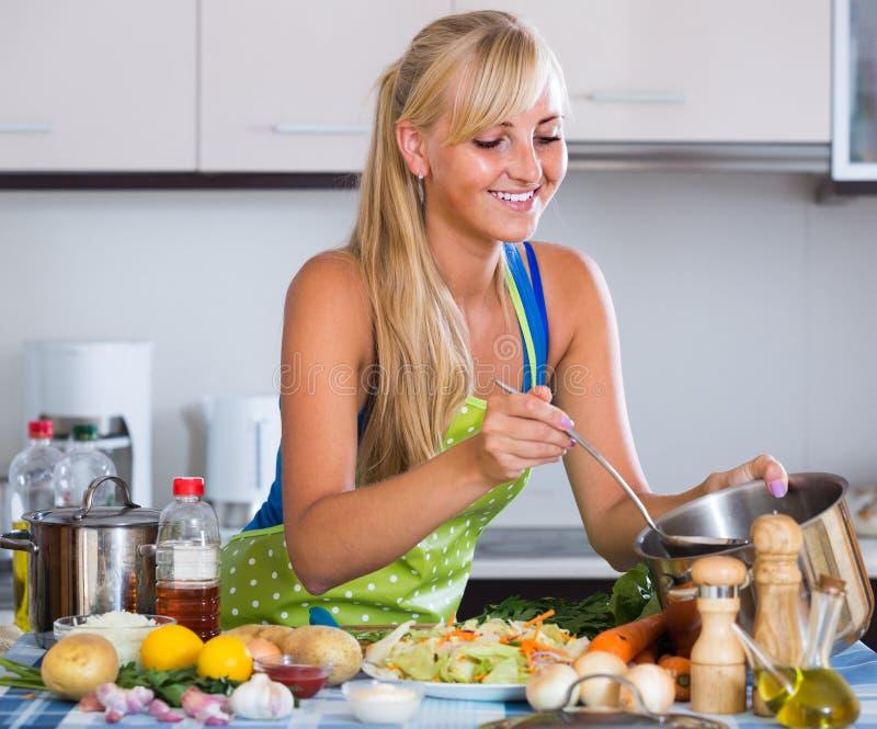 Gladlynt blondie som förbereder veggies i inhemskt kök royaltyfri bild