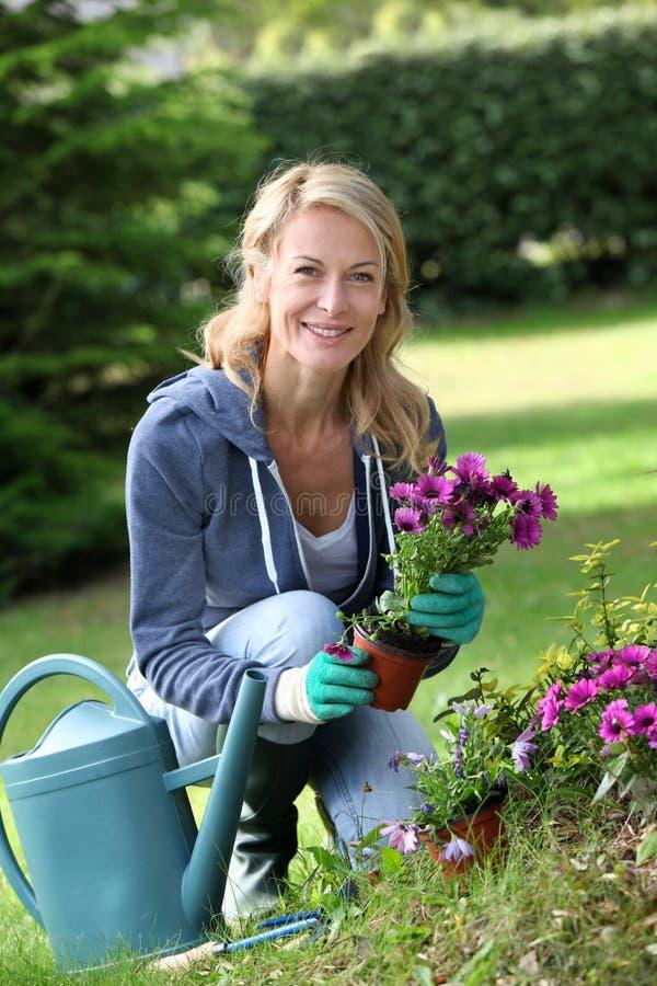 Gladlynt blont arbeta i trädgården för kvinna arkivfoton