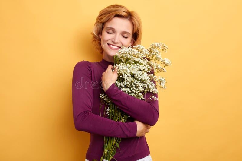 Gladlynt blont krama för kvinna som omfamnar blommor royaltyfri foto