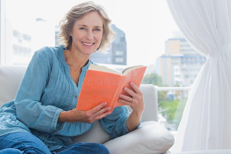 Gladlynt blont kvinnasammanträde på hennes soffa som rymmer en bok arkivfoton