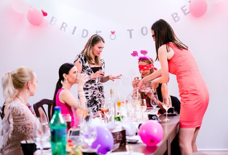 Gladlynt brud och brudtärnor som firar möhippan med drinkar arkivbilder