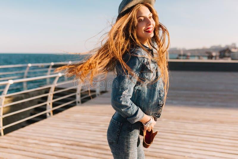 Gladlynt brunettflicka med dagligt smink som hoppar på pir som poserar på bakgrund och att le för hav slankt kvinnabarn royaltyfria bilder