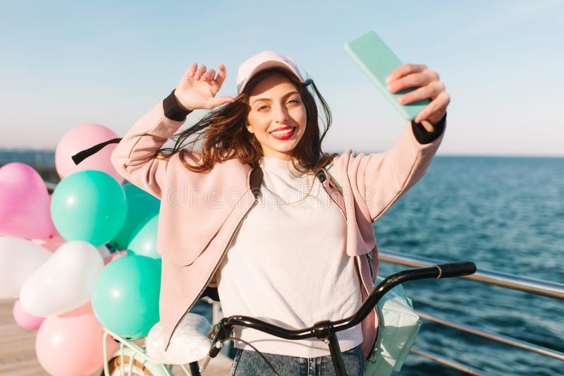 Gladlynt brunettflicka på cykeln som har gyckel i blåsig morgon på havspir efter cykelritt Charma den unga kvinnan in arkivfoto
