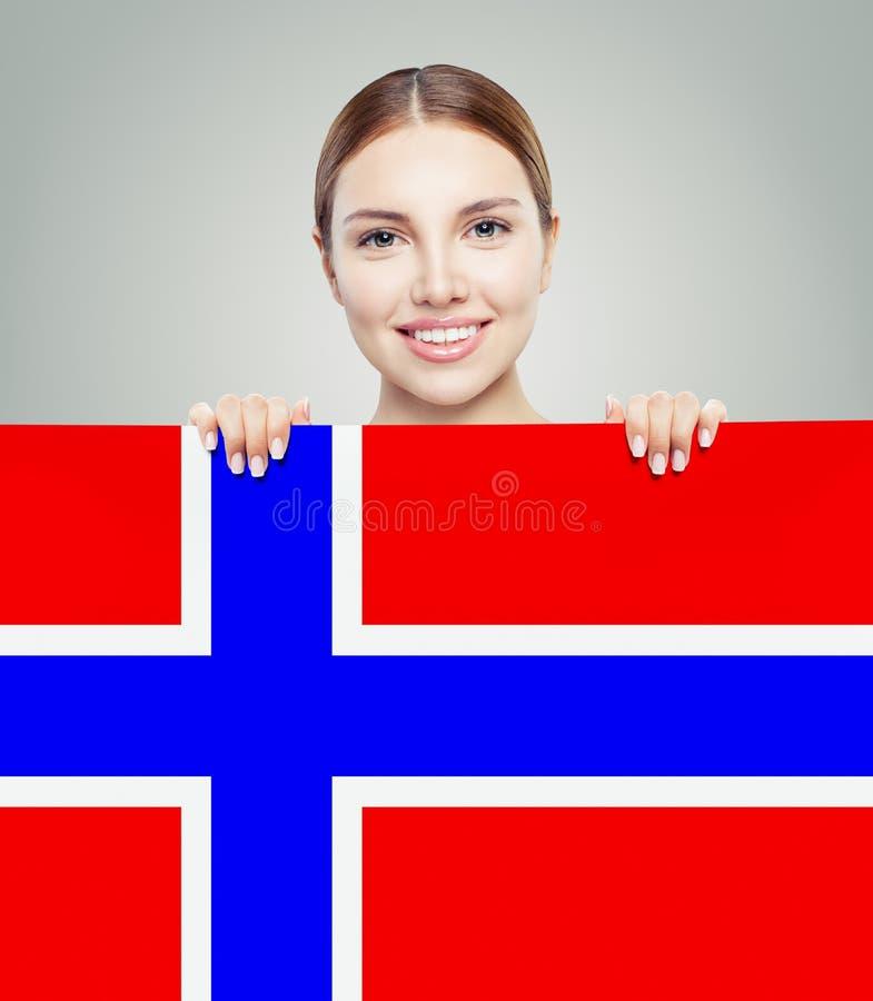 Gladlynt brunettkvinnavisning med den Norge flaggabakgrunden arkivfoton