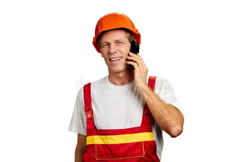 Gladlynt byggmästare som talar på mobiltelefonen arkivbild