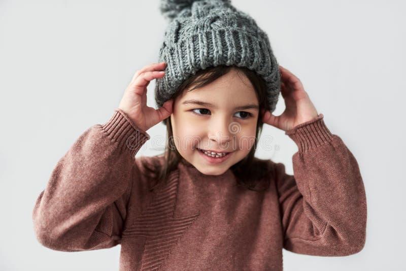 Gladlynt Caucasian liten flicka i tröjan för hatt den vinter som varma gråa för le och bära, isoleras på en vit studiobakgrund royaltyfri bild