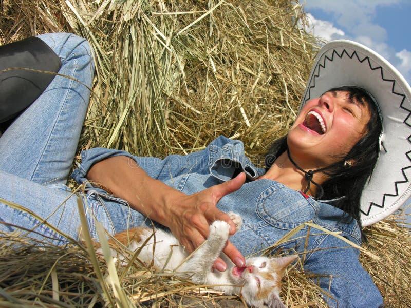 Gladlynt cowgirl som leker med den roliga kattungen royaltyfria bilder