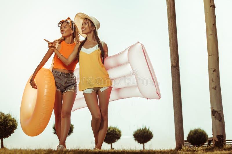 Gladlynt damöverskrift till stranden med uppblåsbar vattenleksaker royaltyfria foton