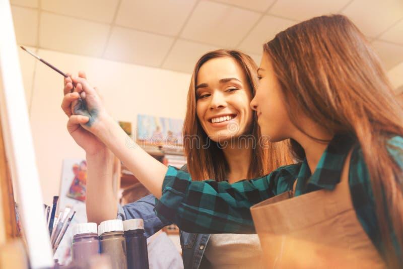 Gladlynt dam som hjälper den tonårs- flickan med målning fotografering för bildbyråer