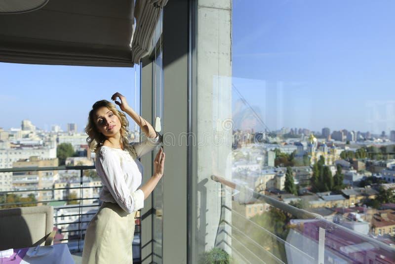 Gladlynt damanseende på restaurangen nära fönster med cityscapebakgrund royaltyfria foton
