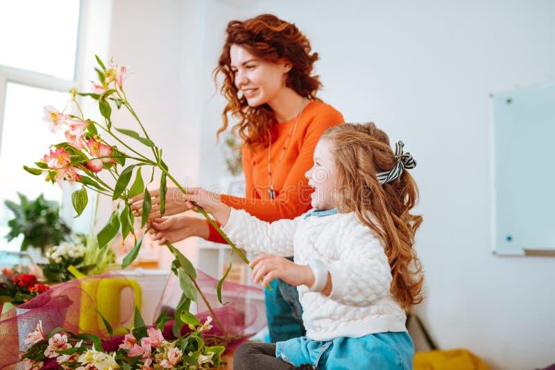 Gladlynt dotter som har rolig stund som ser blommor med mamman royaltyfria foton