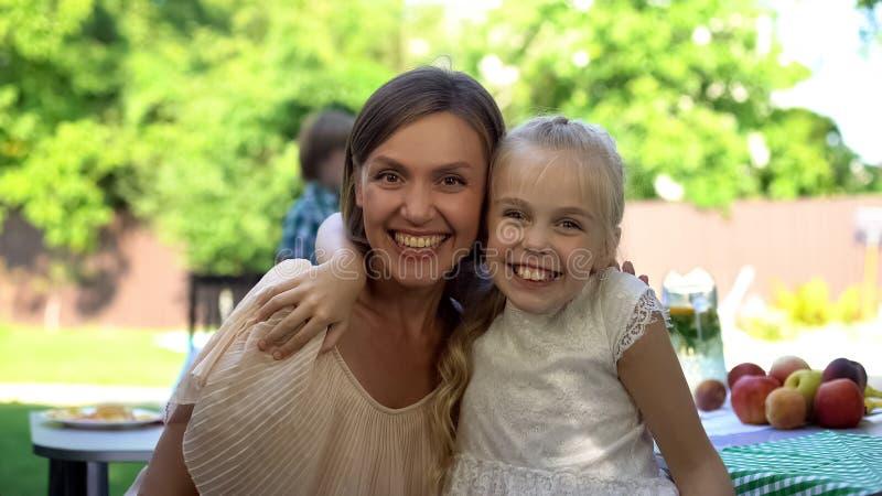 Gladlynt dotter som kramar den lyckliga modern, förtroendefull familjförbindelse, samhörighetskänsla arkivfoto