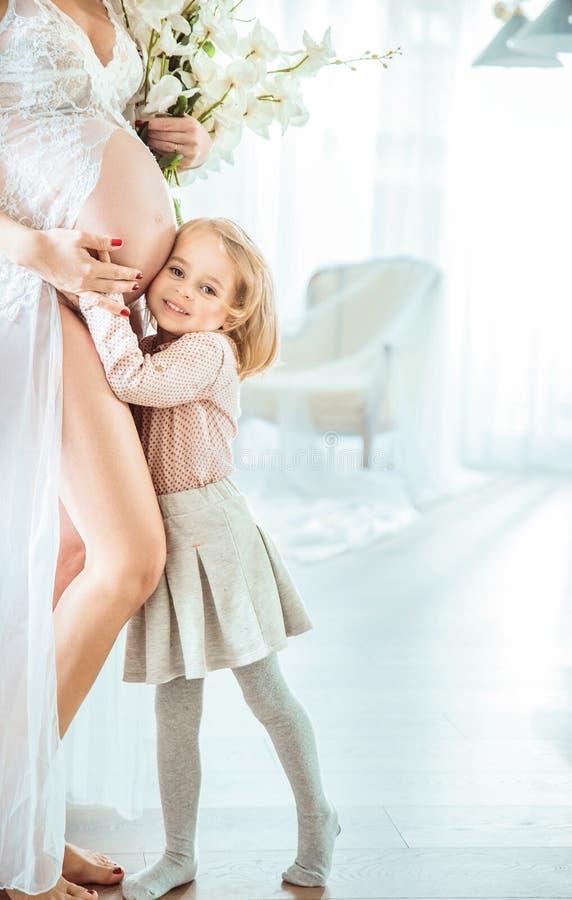 Gladlynt dotter som kramar hennes buk för moder` s royaltyfria foton