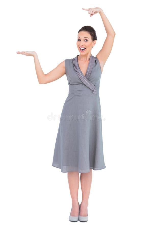 Gladlynt elegant kvinna i flott klänningvisningriktning royaltyfria bilder