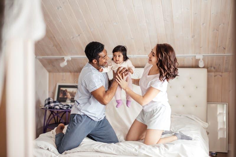 Gladlynt enorm man och kvinna som rymmer deras lilla barn och spelar med henne arkivbild