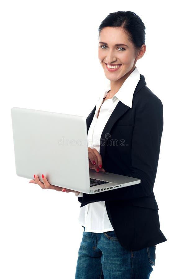 Gladlynt företags kvinna som använder bärbara datorn arkivfoto