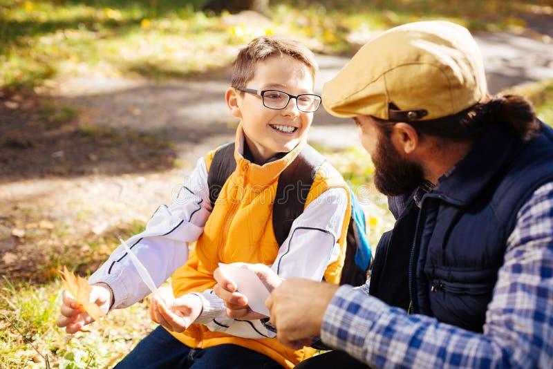 Gladlynt förtjust pojke som rymmer en lönnlöv arkivfoto