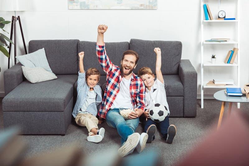 gladlynt fader med söner som lyfter händer, medan hålla ögonen på fotbollsmatchen arkivbild