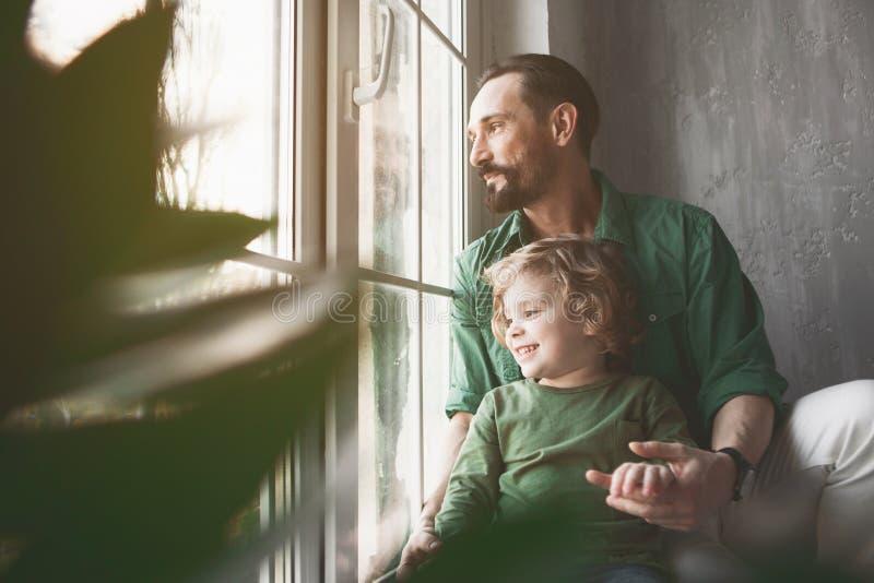 Gladlynt fader och barn som håller ögonen på på gatan arkivbild