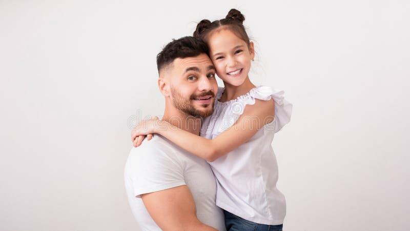 Gladlynt fader och dotter som omfamnar, studiostående arkivfoto