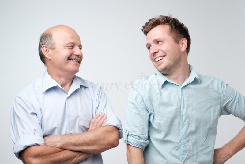 Gladlynt fader och son som ser de som ler arkivfoto