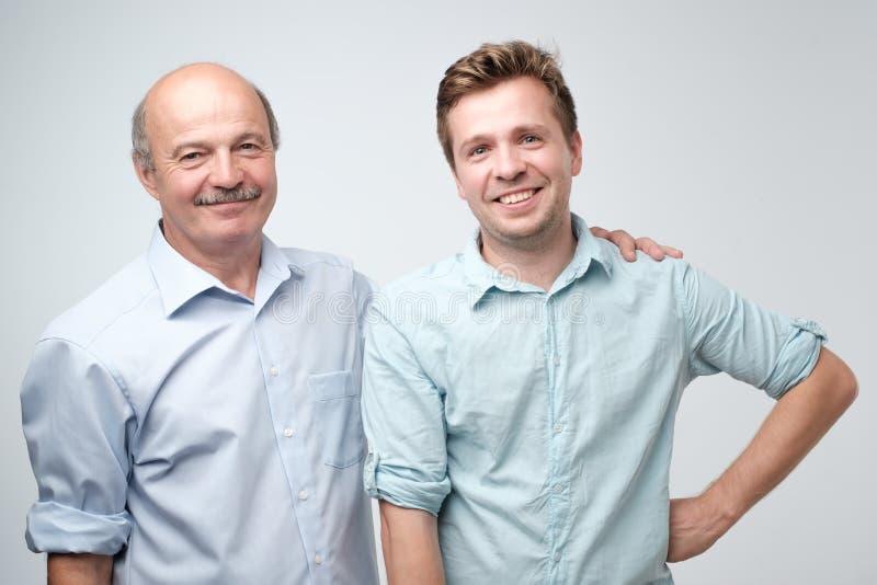 Gladlynt fader och son som tillsammans kramar och poserar fotografering för bildbyråer