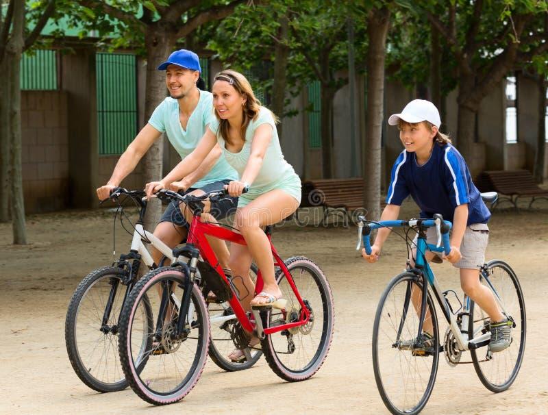 Gladlynt familj av tre som cyklar på stadsvägen arkivbild