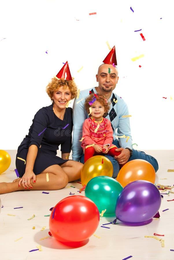 Gladlynt familj på partiet med konfettier arkivbilder