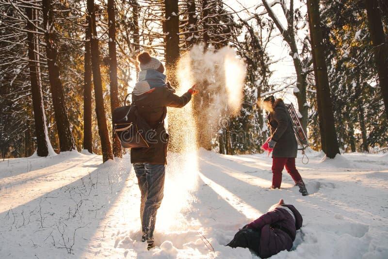 Gladlynt familj som skrattar i vinterskog arkivfoton