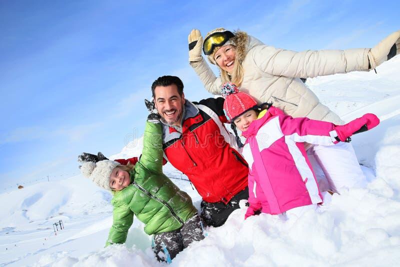 Gladlynt familj som spelar i snö tillsammans arkivfoto