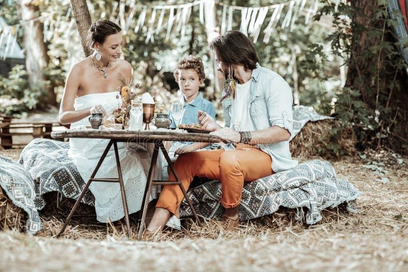 Gladlynt familj som tillsammans äter i trädgården arkivfoton