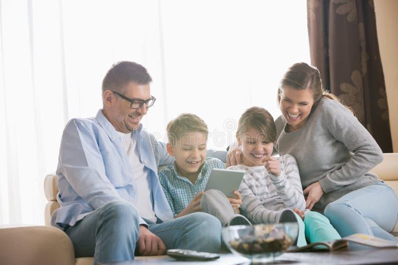 Gladlynt familj som tillsammans använder minnestavlaPC i vardagsrum arkivfoton
