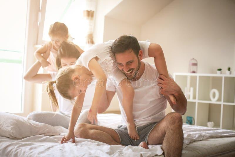 Gladlynt familj som tillsammans spelar på säng royaltyfria foton