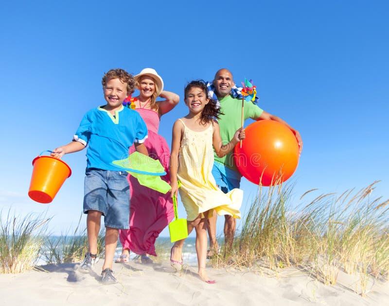Gladlynt familjbindning vid stranden royaltyfri fotografi
