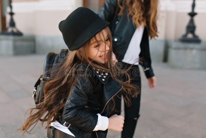 Gladlynt fantastisk flicka med långt hår som vinkar ha roligt utomhus- gå i fyrkanten med mamman Älskvärt barn i moderiktigt royaltyfri fotografi