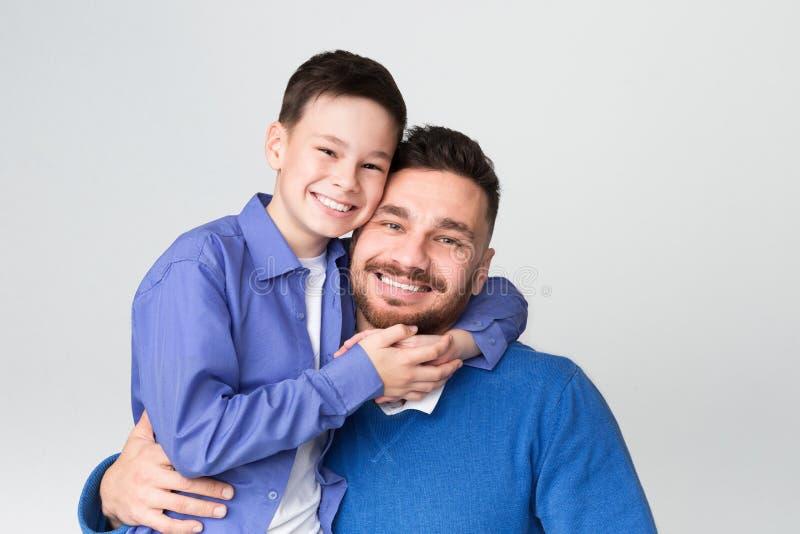 Gladlynt farsa och son som omfamnar och ler på kameran royaltyfri bild
