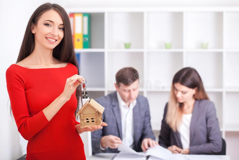 Gladlynt fastighetsmäklare som ger hustangenten till lyckliga egendomsägare, youn royaltyfri foto