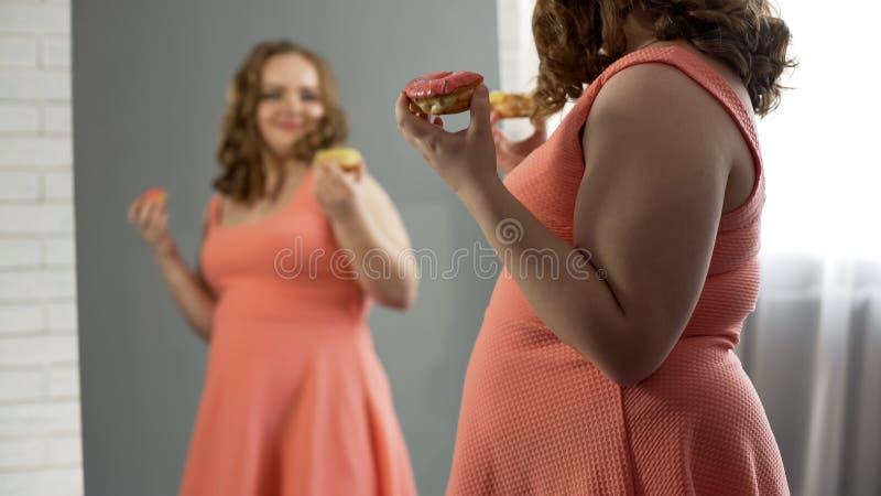 Gladlynt fet flicka som tillfredsställs med hennes utseende som framme äter donuts av spegeln royaltyfri bild