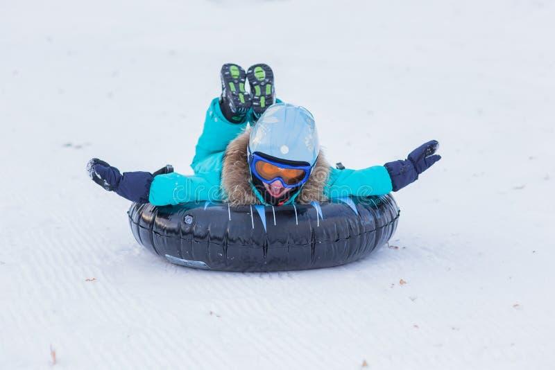 Gladlynt flicka i en hjälm och exponeringsglas som rider på en släde med höga berg arkivfoto