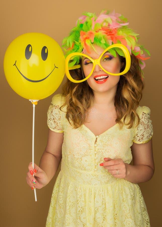 Gladlynt flicka i en ljus peruk och stora exponeringsglas som rymmer en ballong fotografering för bildbyråer