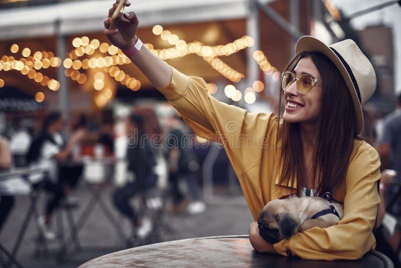 Gladlynt flicka i exponeringsglas som gör selfie med att sova mopshunden arkivbild