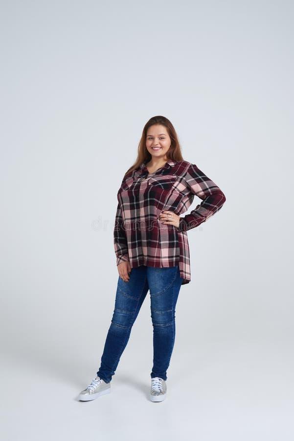Gladlynt flicka i lös skjorta som ler på kameran royaltyfri foto