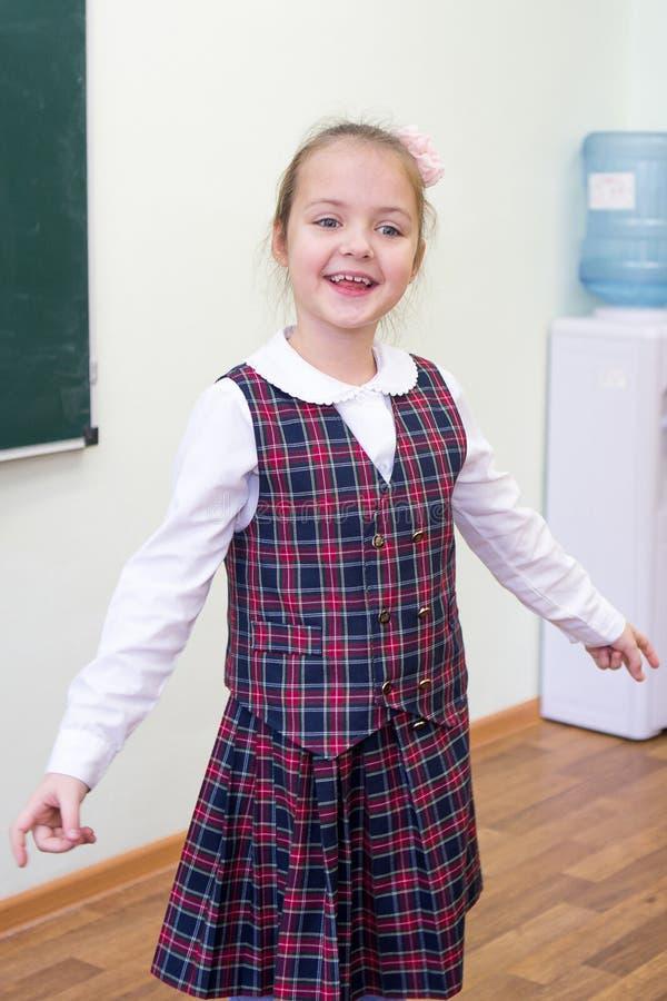 Gladlynt flicka i skolagrupp pojken lärer den huvudlästa skolalärare till Stående av ett barn royaltyfri fotografi