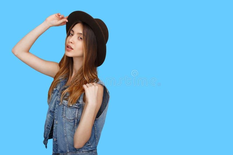 Gladlynt flicka i tillfällig kläder, hatt som står, i profilen och att se som isoleras över blå bakgrund royaltyfria bilder