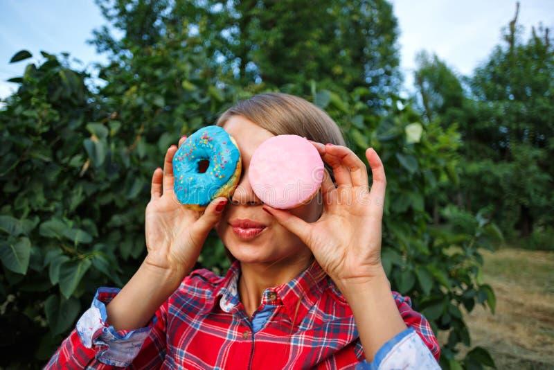 Gladlynt flicka och exponeringsglas av donuts royaltyfri foto