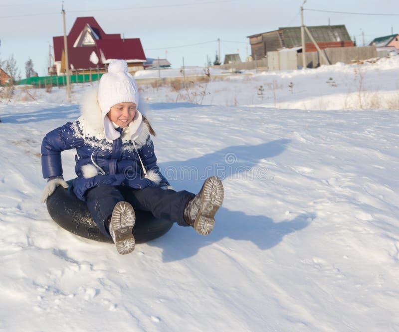 Gladlynt flicka på en snöig kulle fotografering för bildbyråer