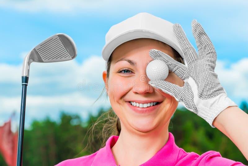 Gladlynt flicka på golfbanan med utrustning arkivfoton